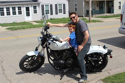 A man and his young son sitting on a white Yamaha Bolt motorcycle