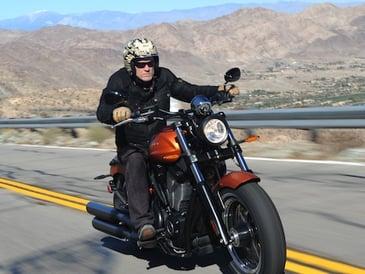 man riding an orange harley davidson motorcycle and wearing a half face helmet