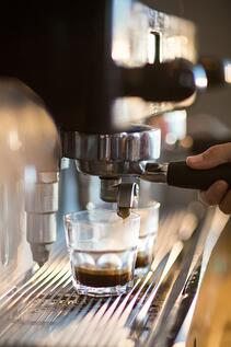 Waitress making cup of coffee in cafx92xA9